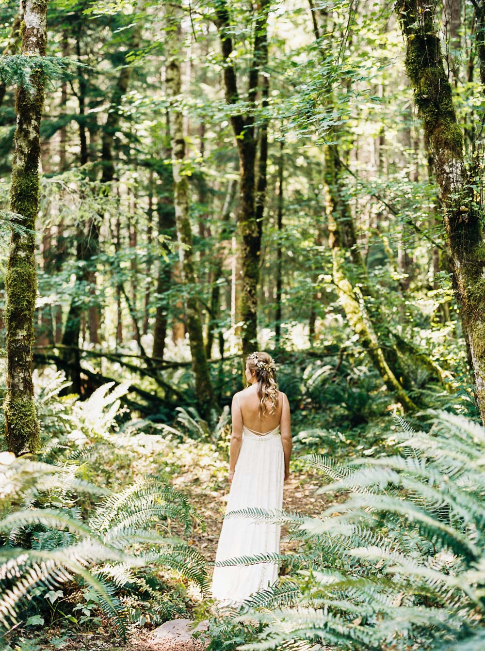 Bride wanders through forest at Wellspring Spa Wedding at Mt. Rainier