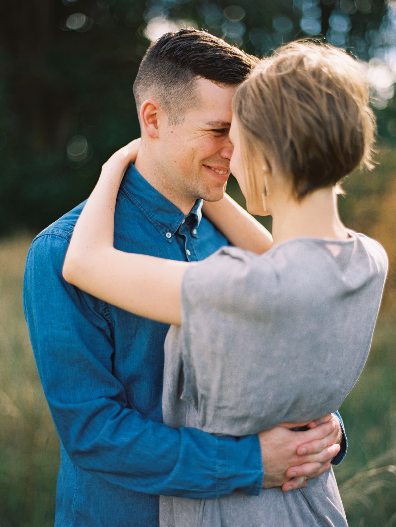 Snuggling close at a discovery park engagement session captured by Seattle FIlm Wedding Photographer Anna Peters