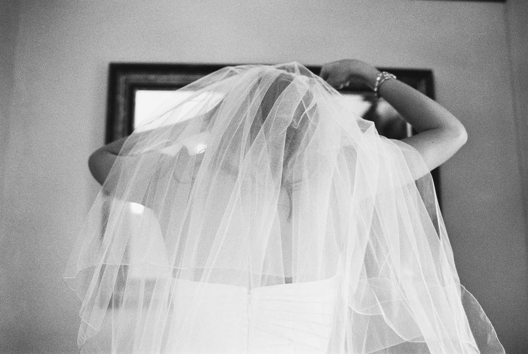 Bride adjusting her veil at Beacon Hill Events with Spokane Wedding Photography by Anna Peters
